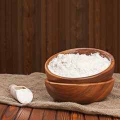 Flour in wooden bowl on nature background.