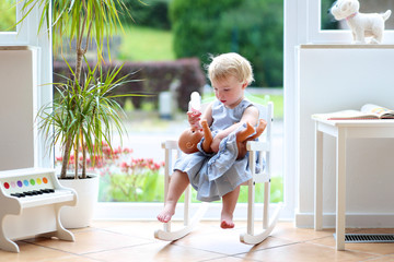 Cute toddler girl playing indoors with doll