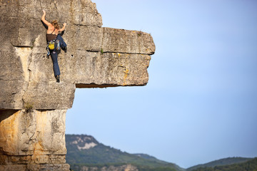 Young female free climber on a cliff