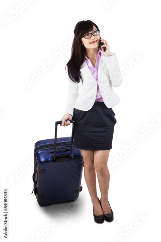 Businesswoman with suitcase and phone