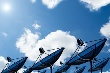black antenna communication satellite dish on blue sky