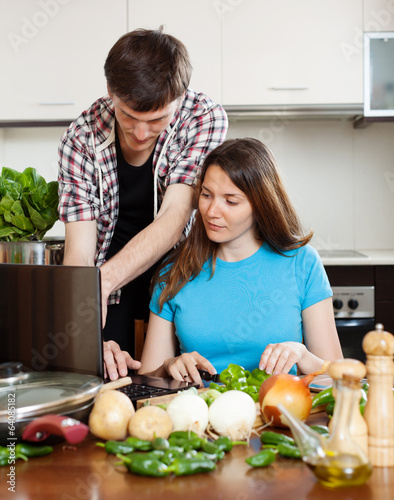 couple looking notebook during cooking vegetables