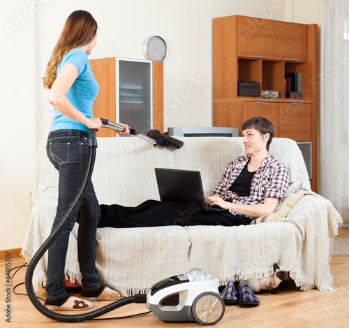 Girl doing sofa cleaning with vaccuum cleaner