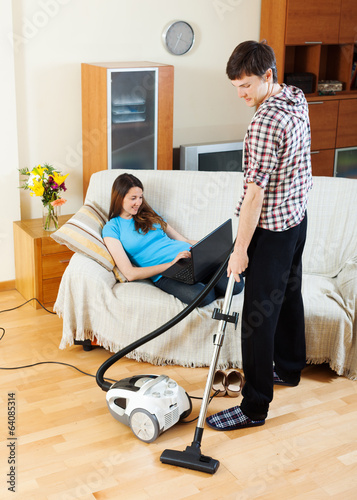 man cleaning  while girl lying with notebook