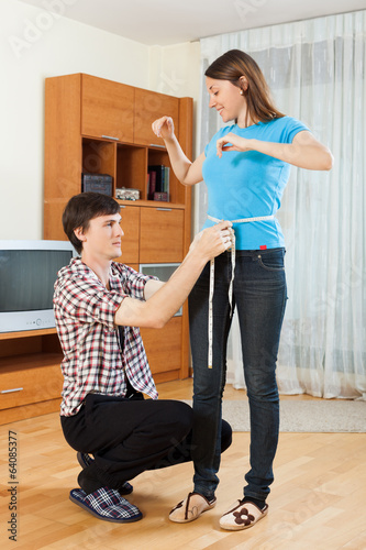 Guy measuring waist of girl