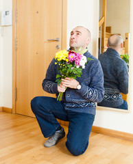 man asks forgiveness with    flowers.