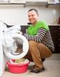 Smiling  man putting clothes in to washing machine