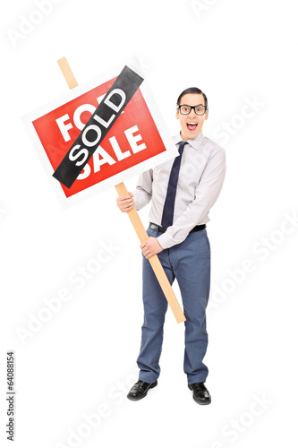 Male realtor holding a sold sign