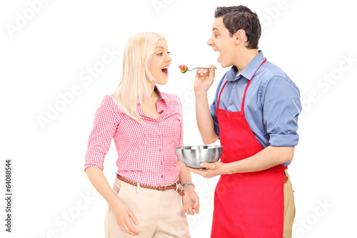 Young man feeding his wife