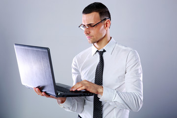 Handsome businessman in glasses using laptop