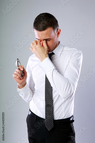 businessman holding glasses and rubbing his eyes