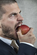 angry businessman eating an apple