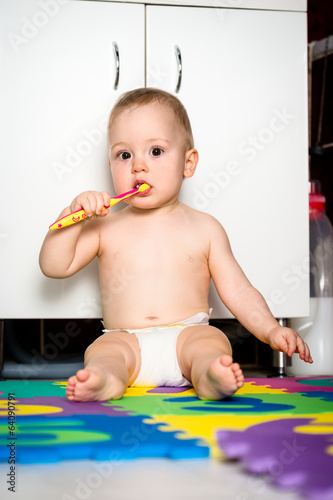 Baby cleaning teeth in bathroom