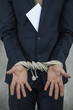 businessman hands are tied from bribes