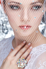 Beautiful white-headed girl in a veil on a silvery background