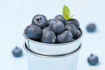 Fresh blueberries in a metal bucket, selective focus
