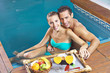 Couple eating breakfast in swimming pool