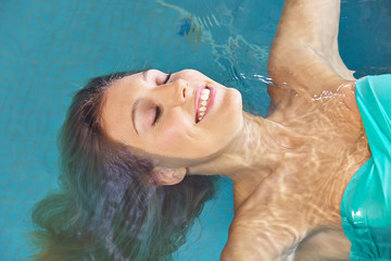 Relaxed woman on back in swimming pool
