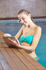 Woman with tablet PC in swimming pool