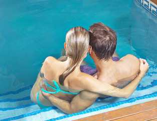 Couple from behind in swimming pool
