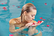 Woman relaxing in water with roses