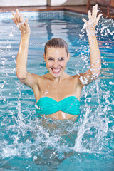 Woman in swimming pool splashing water