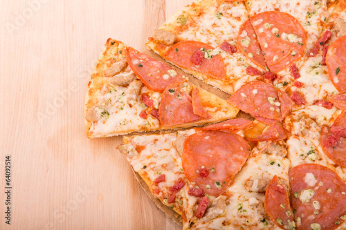 Sliced Pepperoni Pizza on Wood Cutting Board with Copy Space