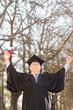 Mature college graduate gesturing success in park