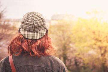 Woman in deerstalker hat looking at trees