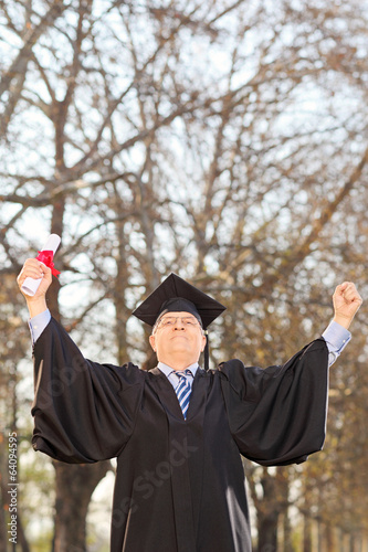 Mature college graduate gesturing success in park