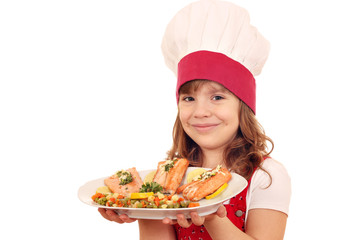 happy little girl cook with salmon and vegetables on dish
