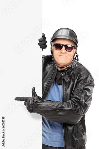 Mature male biker pointing on a black panel