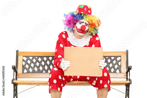 Sad clown holding a blank carton sign