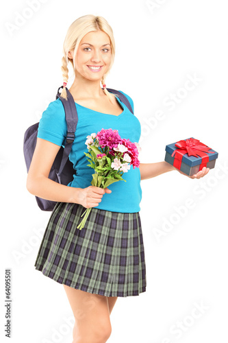 Schoolgirl holding flowers and a gift box