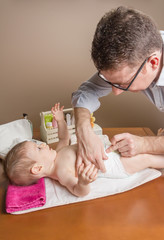 Father changing diaper of adorable baby