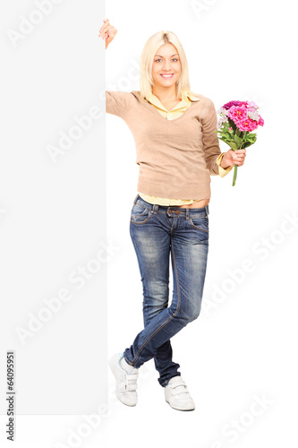 Woman holding flowers next to a blank panel