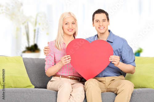 Young couple holding a big red heart at home