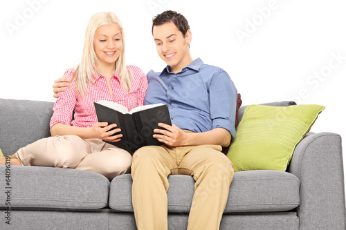 Young couple reading book seated on a couch