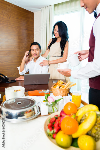 Asian room waiter serving food in hotel