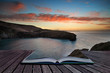 Book concept Beautiful vibrant sunrise over rocky coastline