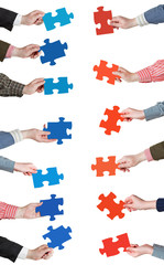 red and blue puzzle pieces in people hands