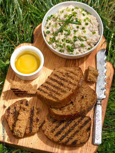 Fresh homemade creamy pate with slice of bread on wooden board