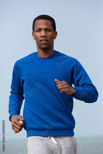 Portrait of a young athletic man jogging