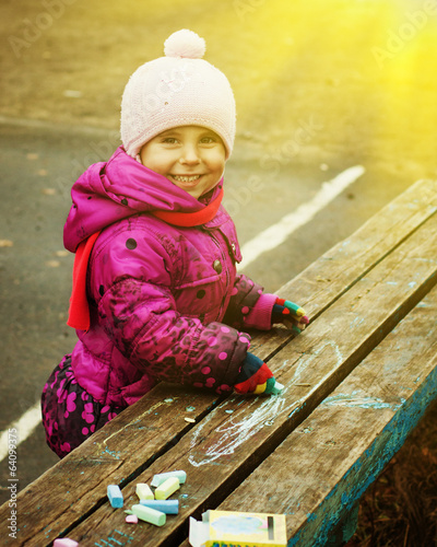 Child draws with chalk.