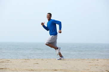 Smiling man jogging at the beach