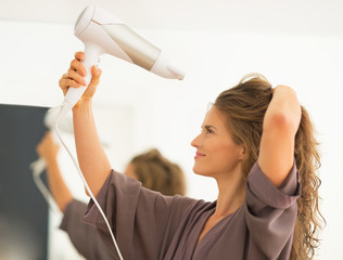 Young woman blow drying hair in bathroom
