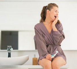 Young woman with toothbrush yawning