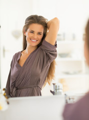 Happy young woman with long hair looking in mirror in