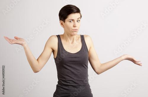 canvas print picture Junge, braunhaarige Frau zuckt mit den Schultern