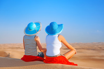 Two girls in hats relaxing at the desert safari